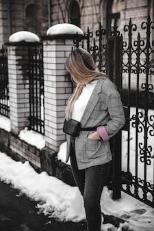 Mode junge frau, die schwarzen hut karierte manteljacke handtasche trägt