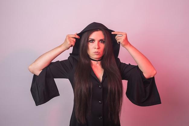 Mode junge frau, die zur halloween-party geht. hexe karnevalskostüm. porträt des sexy mädchens im schwarzen kleid.