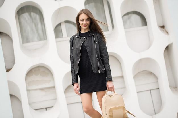 Mode junge frau in einem schwarzen felsen auf einem weißen wandhintergrund
