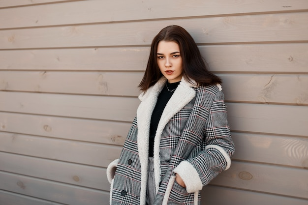 Mode junge frau in stilvoller outwear mit vintage-mantel steht ordentlich einen hölzernen hintergrund