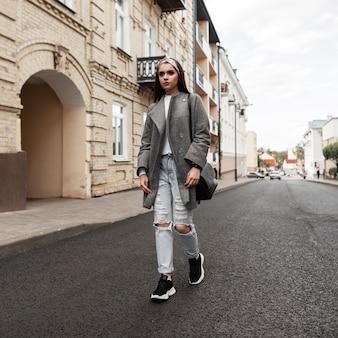 Mode junge frau in trendigem bandana in grauem, stylischem mantel in zerrissenen jeans in turnschuhen mit schwarzer tasche gehen in der nähe von vintage-gebäuden im freien. schönes mädchen in modejugend beiläufige frühlingskleidung genießt reisen