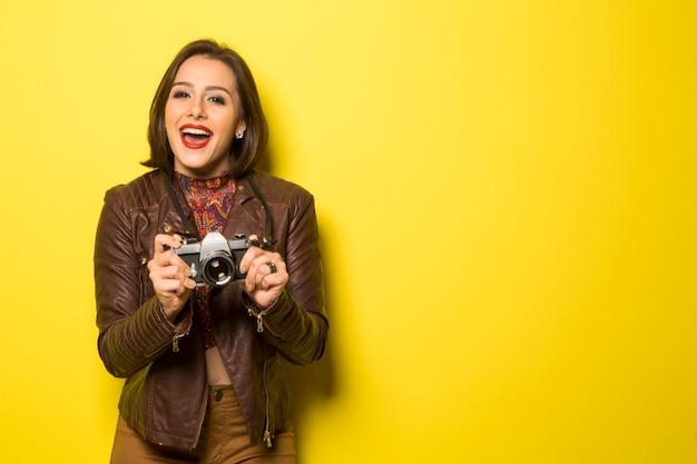 Mode junge frau macht das foto mit alter kamera auf gelber wand
