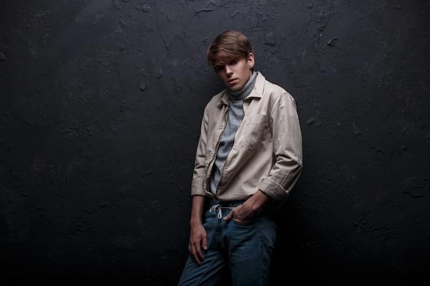 Mode junger mann in einer leichten stilvollen jacke im trendigen pullover mit einem modischen haarschnitt in vintage blue jeans, die drinnen nahe der wand aufwirft. netter kerl. herrenbekleidung im amerikanischen stil