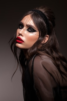 Mode junges modell mit schwarzen professionellen katzenaugen make-up rote lippen trendige frisur perfekte haut