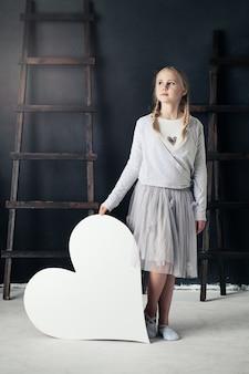 Mode-kindermädchen und großes weißes herz. modeporträt