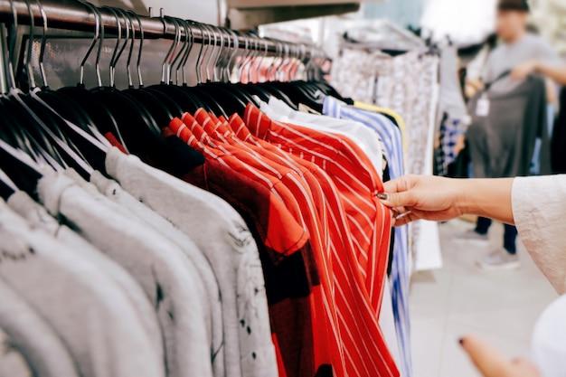 Mode-konzept. frau, die kleidung auf gestell im butikenspeicher im einkaufszentrum wählt