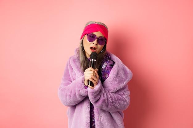 Mode-konzept. stilvolle ältere asiatische frau, die karaoke singt, auf der bühne mit mikrofon aufführt, trendige sonnenbrille und lila kunstpelzmantel trägt, rosa hintergrund