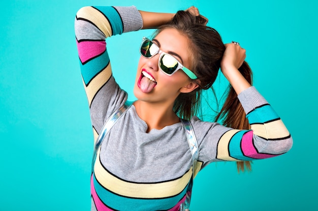 Mode-lifestyle-porträt einer freudigen lustigen frau, sexy volle lippen, verspiegelte sonnenbrille, die ihre haare wie zwei pferdeschwänze, frühlingsfarben, minzhintergrund hält. süße emotionen, trendige frau.