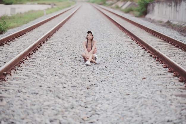 Mode-lifestyle-porträt einer jungen asiatischen frau, die entlang der bahngleise sitzt; junge frau auf eisenbahnschiene.