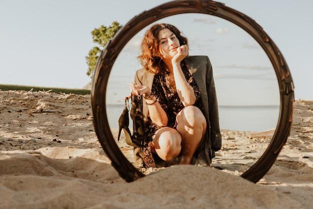 Mode-lifestyle-porträt einer jungen trendigen frau, gekleidet in ein schwarzes kleid und eine lachende jacke, die am strand im spiegelbild posieren