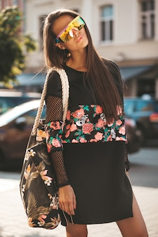 Mode lustige glamour stilvolle sexy lächelnde schöne junge frau modell in schwarzen hipster sommerkleidung in der straße nach dem einkaufen