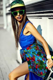 Mode lustiger glamour stilvoll sexy lächelnd schönes junges frauenmodell in blauen hipster-sommerkleidung in der straße in der mütze