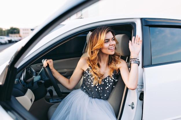 Mode mädchen im tüllrock, der weißes auto fährt. sie gratulierte jemandem zur seite.