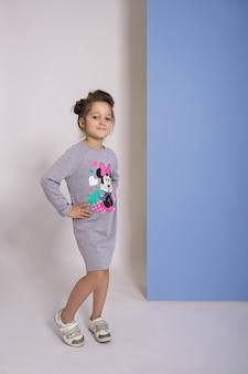 Mode mädchen in stilvollen kleidern auf farbigem wandhintergrund. herbst helle kleidung auf kinder, ein kind posiert