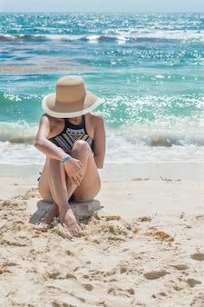 Mode mädchen sitzt an der küste an einem schönen nachmittag, mit dem meer hinter, vorderansicht. frau mit gekreuzten beinen, die auf dem sand sitzen. frau mit sonnenhut. frau, die in der maya-riviera bräunt