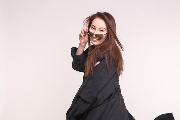 Mode-, model- und people-konzept. junge asiatische frau, die sie über der brille über weiß ansieht.