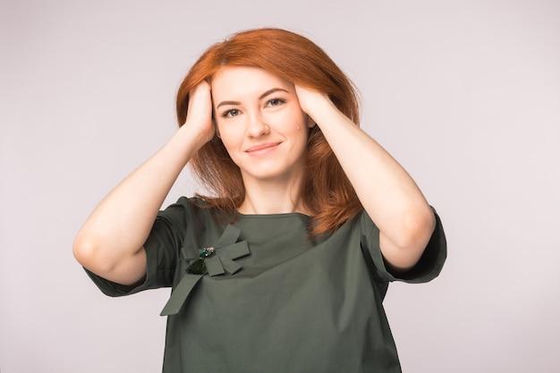 Mode, modeling und menschenkonzept - junge frau versteckt ihre hände in rotem kopf und lächeln.