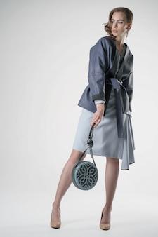 Mode-modell, das in der kleidung auf weißem hintergrund aufwirft
