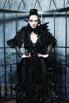 Mode-modell im fantasiekleid, das im stahlkäfig aufwirft.