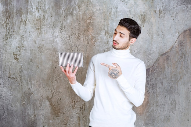 Mode-modell im weißen pullover mit einer silbernen geschenkbox.