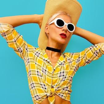 Mode-modell im wild-west-stil. trendige accessoires hut und sonnenbrille. schönes kariertes hemd
