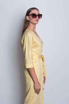 Mode-modell in der großen sonnenbrille, die gelbes kleid mit den knöpfen aufwirft über grau trägt