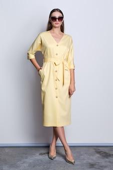 Mode-modell in der großen sonnenbrille, die gelbes kleid mit den knöpfen aufwirft über grauem hintergrund trägt