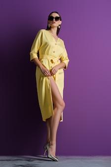 Mode-modell in der großen sonnenbrille, die gelbes kleid mit gelösten knöpfen trägt