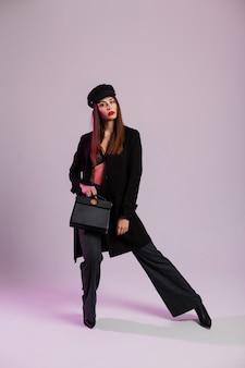 Mode-modell junge frau in elegantem spitzen-bh in mütze in jacke in hose in stiefeln mit lederhandtasche steht im raum in der nähe der wand. sexy mädchen mit braunen haaren posiert in stilvoller schwarzer kleidung drinnen