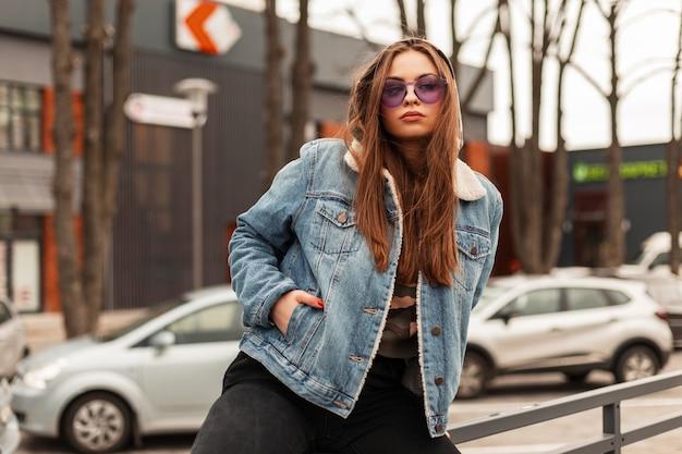 Mode-modell junge schöne frau in modischer übergroßer blauer jeansjacke mit kapuze mit lila glamouröser brille, die in der nähe der straße in der stadt posiert. hipster-städtisches mädchen im freien. amerikanischer stil