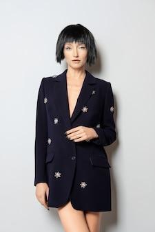 Mode-modell mit dem schwarzen pendelhaarschnitt, der nahe der wand in der blauen jacke mit edelsteindekor aufwirft