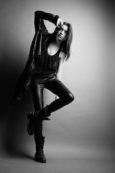 Mode-modell mit lederhose und jacke posiert auf grauem hintergrund