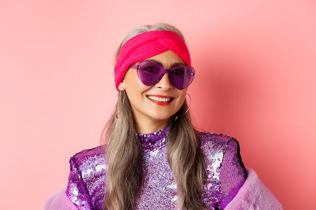 Mode. nahaufnahme einer stilvollen älteren frau, die glücklich in die kamera lächelt, sonnenbrille und disco-stirnband trägt, rosa hintergrund