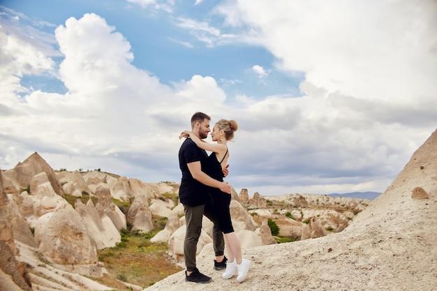 Mode-ostpaar, das mit bergen im hintergrund umarmt. mann und frau liebende beziehung. schöne berge