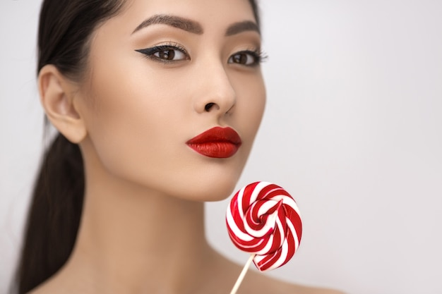 Mode-porträt der asiatischen frau mit lutscher im studio