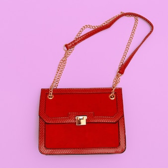 Mode rote damenkupplung auf rosa hintergrund. konzept im flat-lay-stil