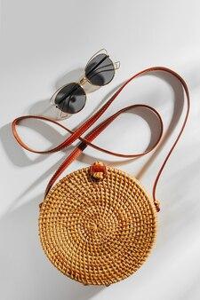 Mode runde bambustasche und sonnenbrille. flache lage, ansicht von oben. modekonzept frühjahr/sommer.