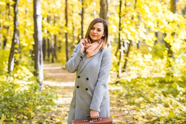 Mode-, saison- und personenkonzept - glückliche junge frau macht eine reise mit retro-koffer auf einem