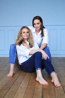 Mode schöne frau im weißen hemd und in den jeans, die zusammen aufwerfen