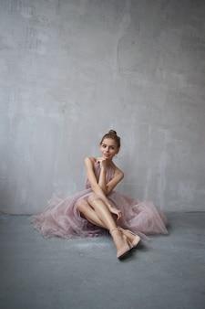 Mode schöne frau in einem kleid, das auf boden gegen die wand sitzt. perfektes make-up, romantisches porträt