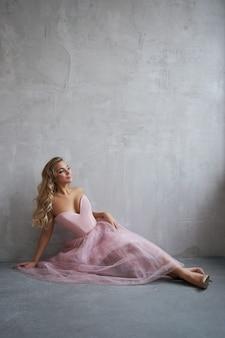 Mode schöne frau in einem kleid, das auf dem boden gegen die wand sitzt. perfektes make-up, romantisches porträt