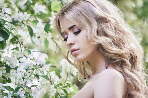 Mode schöne junge frau, umgeben von lila blumen