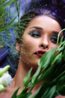 Mode schönes mädchen mit hellem make-up unter blumen.