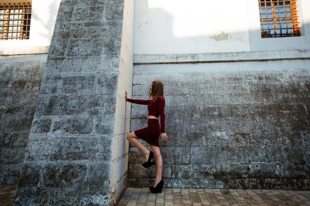 Mode-schönheitsporträt. schöne frau mit lockigem haar in einem modischen roten kleid, das an der wand stand, schloss seine augen