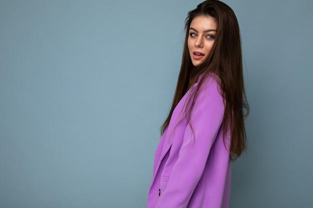Mode-schuss der jungen sexy glücklichen attraktiven brunettefrau, die stilvollen violetten anzug trägt, der auf blauem hintergrund mit leerem raum lokalisiert wird. unternehmenskonzept