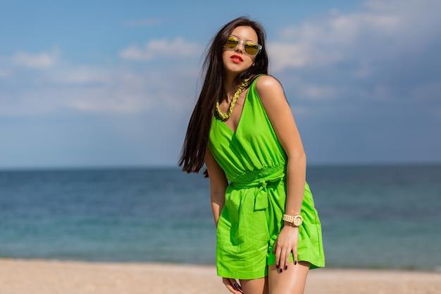 Mode-sommerporträt im freien der schönen jungen frau der hübschen jungen brünette in der kühlen sonnenbrille, die auf dem sonnigen tropischen strand aufwirft.