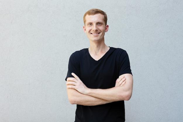 Mode, stil, emotionen und menschen-konzept - nahaufnahme porträt einer rothaarigen eines schönen männlichen mannes mit sommersprossen auf einem grauen hintergrund, schwarzem t-shirt. gekreuzte hände auf der brust