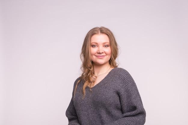 Mode-, stil- und personenkonzept - porträt einer schönen jungen frau mit einem zarten lächeln sie über weiße wand mit kopierraum