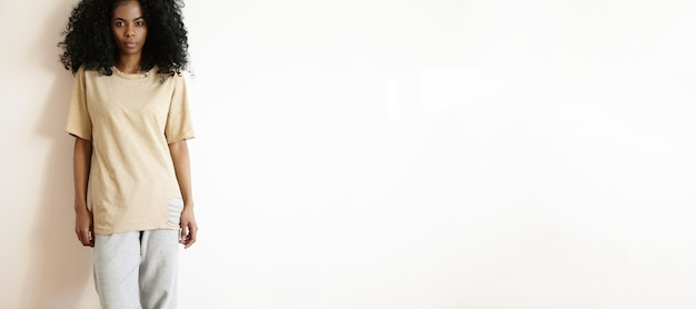 Mode-, stil- und schönheitskonzept. attraktives junges dunkelhäutiges weibliches modell, das freizeitkleidung trägt, die drinnen an der weißen leeren wand aufwirft