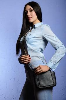 Mode stilvolle brünette mädchen in jeans, die die kamera mit einer tasche betrachten